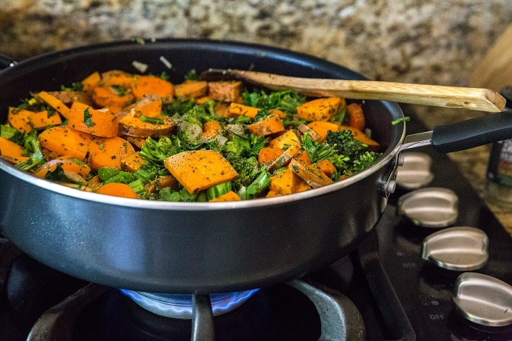 chopped broccoli, carrots, sweet potatoes and onion cooking in a big skillet with seasonings