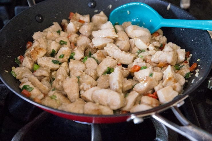 Chicken and vegetables cooking in a skillet for kung pao chicken