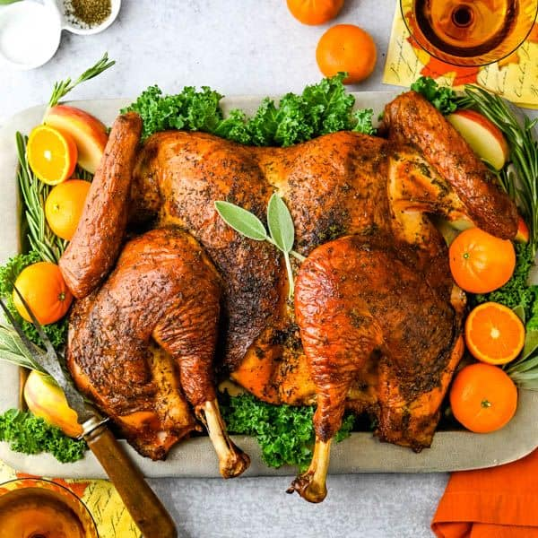 Spatchcook Grilled Turkey with Cider Gravy from Garlic and Zest - Want a delicious, super-moist turkey that doesn't require a 5 gallon brining bucket? This easy dry brine turkey is the answer. Instead of soaking in  liquid brine, an easy 4-ingredient turkey rub infuses the bird with flavor and moisture — and all you need is a sheet pan. Plus, this bird  cooks in about half the time.
