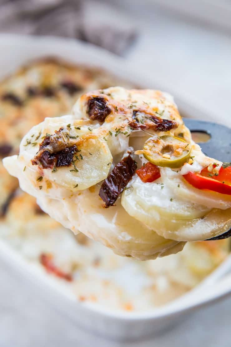 Mediterranean Scalloped Potatoes with sun-dried tomatoes, olives, and roasted bell peppers. A unique spin on classic scalloped potatoes for an amazing side dish!