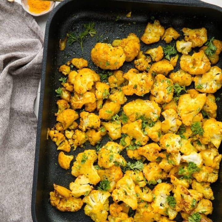 Turmeric Roasted Cauliflower - an easy superfood side dish with cauliflower, turmeric, garlic powder, liquid aminos and sriracha for a flavorful vegan, paleo, keto side dish