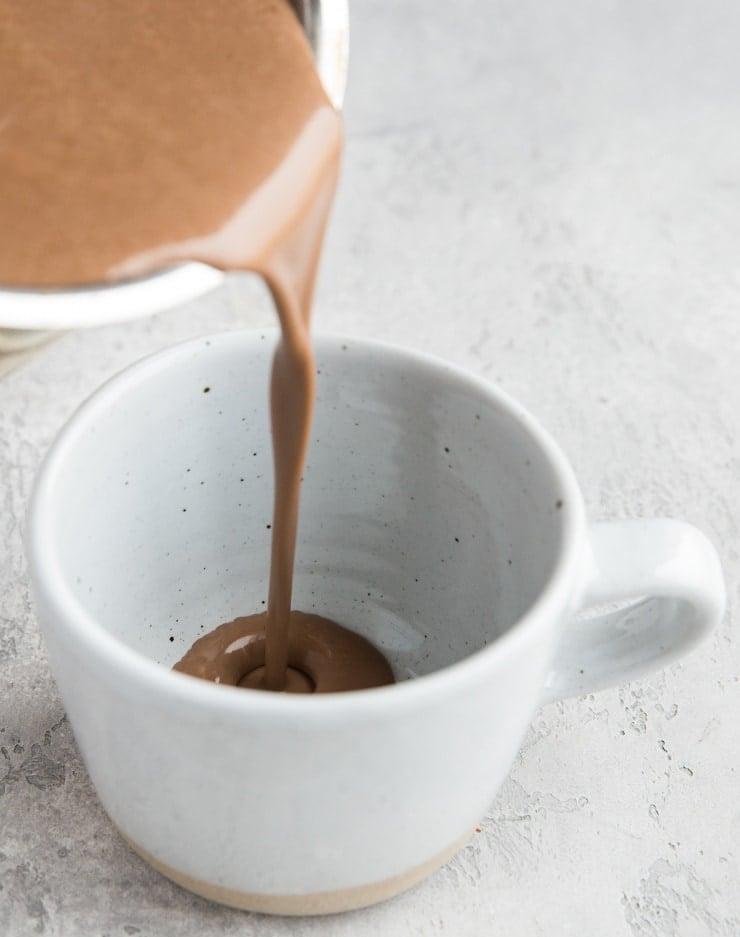 Pouring homemade hot chocolate into a mug