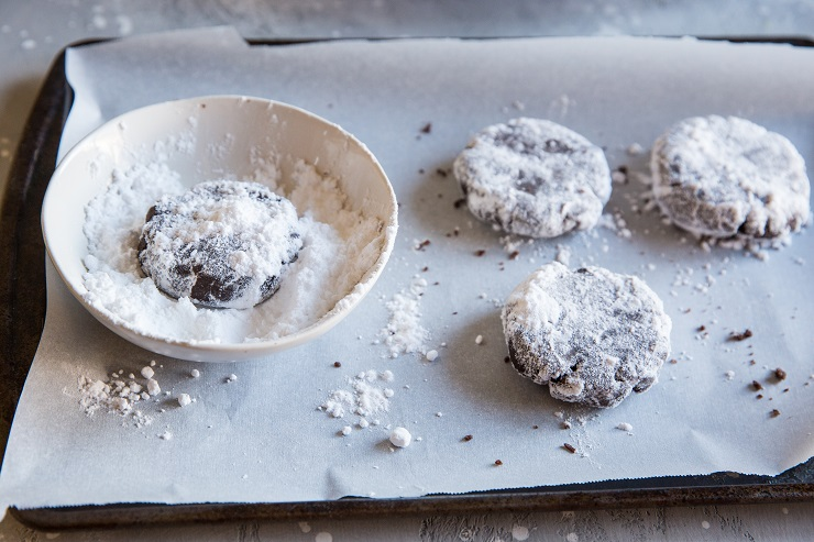 rolling crinkle cookies in confectioners sugar