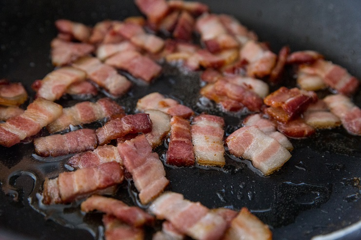 chopped bacon cooking in a skillet