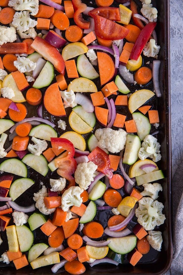 Vegetables for roasted vegetable bowls on a baking sheet