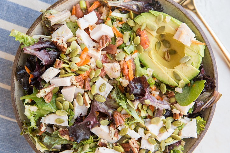 A filling, nutritious salad recipe with spring greens, chicken, avocado, carrots, heirloom tomato, pumpkin seeds, pecans, and more!