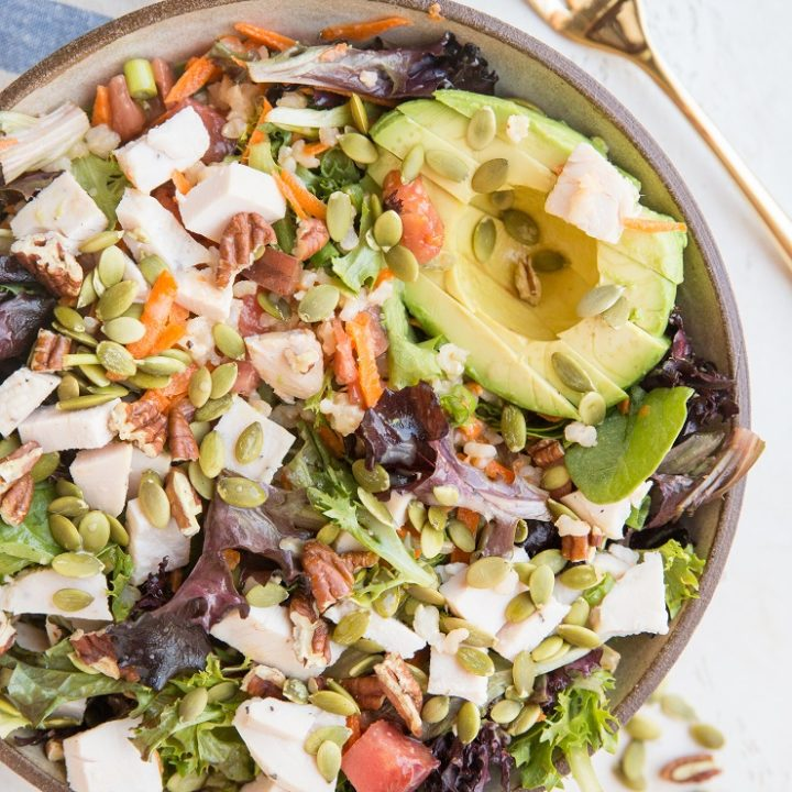 Amazing Filling Salad Recipe with chicken, avocado, spring greens, carrot, pumpkin seeds, pecans, green onion, and tomato