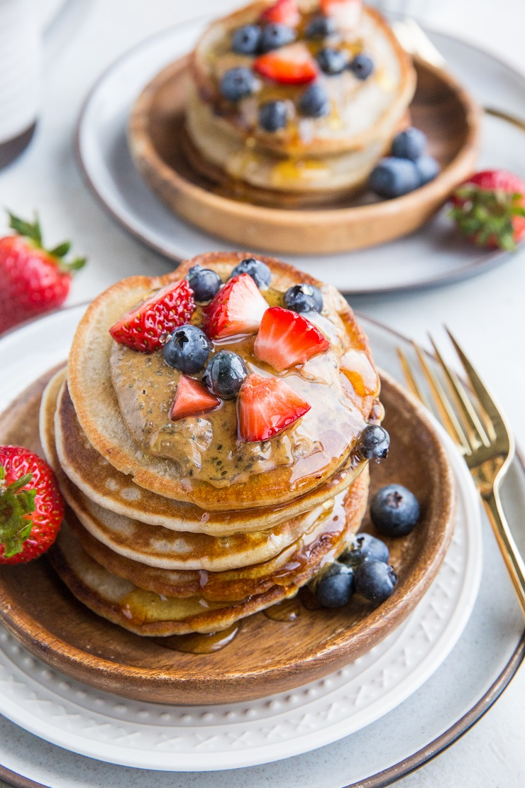 Two plates with stacks of kombucha pancakes with nut butter berries and honey on top