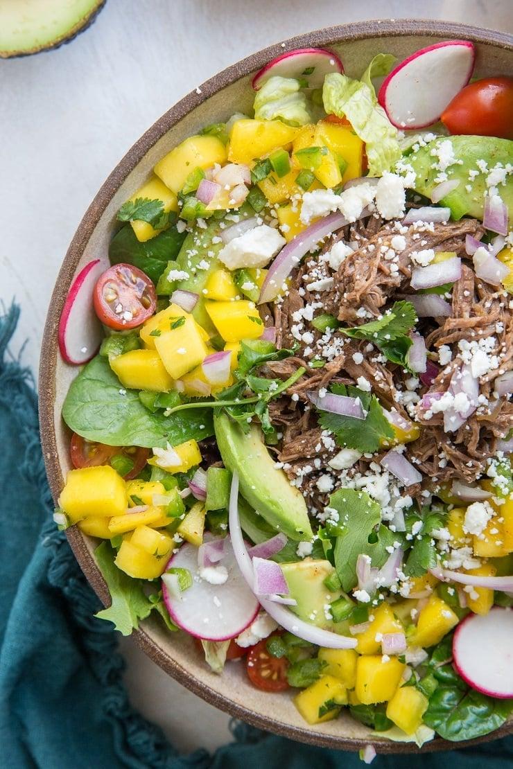 Instant Pot Shredded Beef Taco Salad with mango salsa, queso fresco, avocado and cilantro-lime dressing