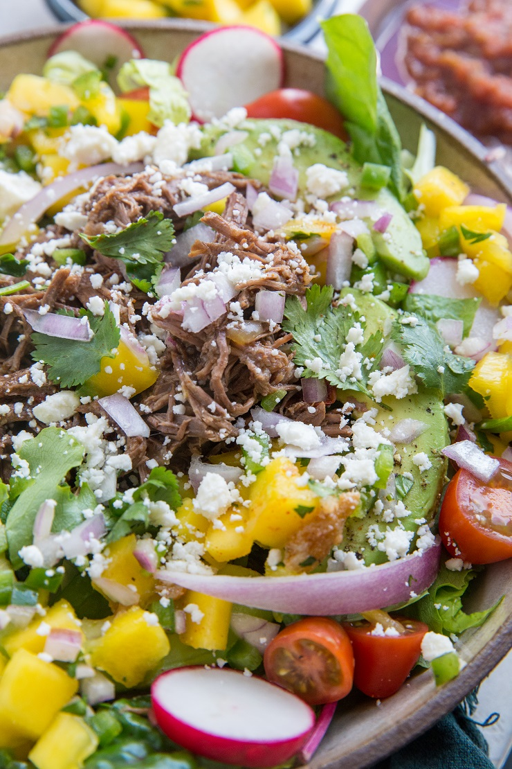 Instant Pot Shredded Beef Taco Salad with mango salsa, avocado and more! A healthy, satisfying entrée salad perfect for dinner. Make it for Cinco de Mayo!.