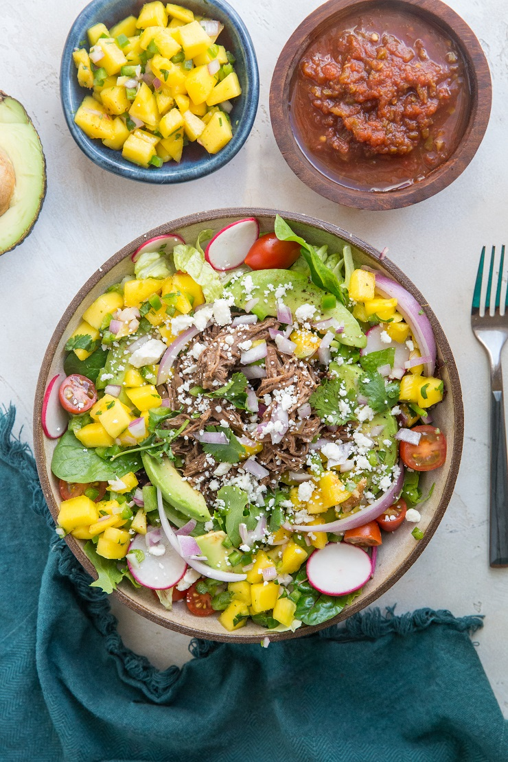 Shredded Beef Taco Salad with spring greens, avocado, cherry tomatoes, mango salsa, and more! A fresh and filling salad recipe!