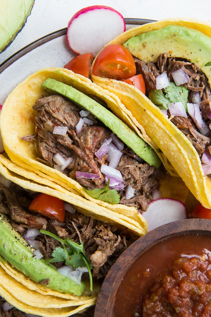 Instant Pot Shredded Beef Tacos with avocado, red onion and salsa. An amazingly flavorful, easy taco recipe!