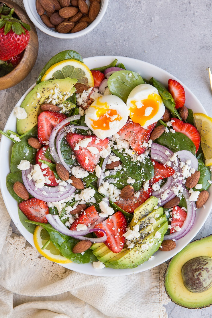 Strawberry Spinach Salad with Poppy Seed Dressing, avocado, roasted almonds, feta, and red onion! A beautiful, delicious salad recipe for any gathering! Amazing side dish or main entrée. Just add chicken!