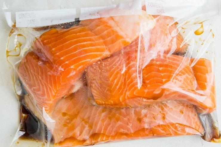 Salmon marinating in teriyaki sauce in a zip lock bag.
