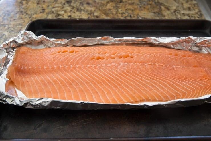 large salmon fillet on foil on a baking sheet