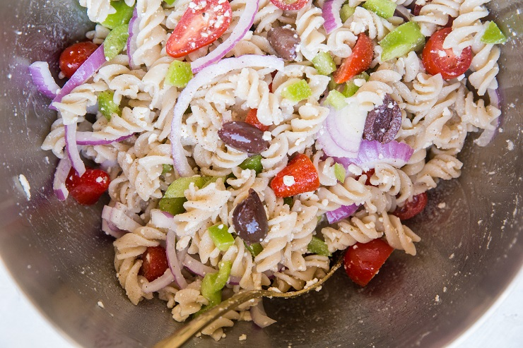Toss ingredients for pasta salad together in a mixing bowl.