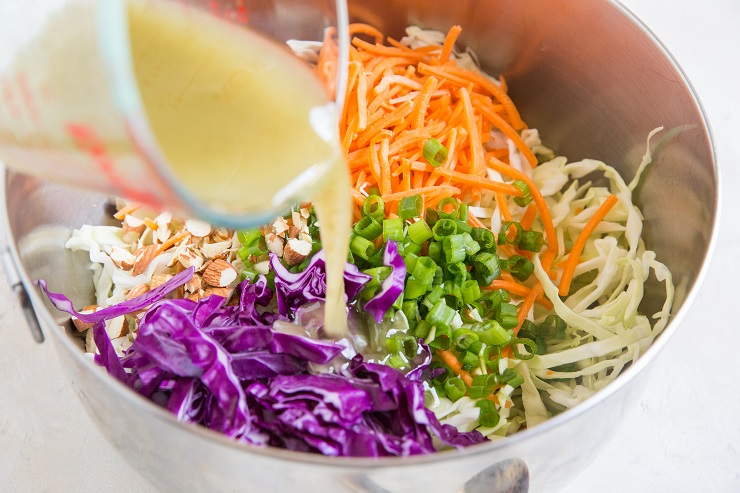 Pour the coleslaw dressing into the mixing bowl with the veggies