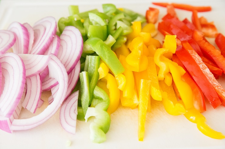 Chopped onions and peppers on a cutting board