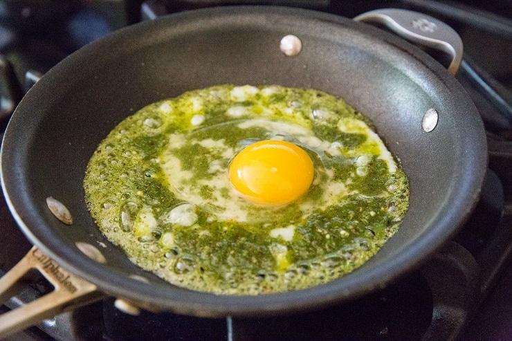 Crack an egg into the center of the pesto sauce
