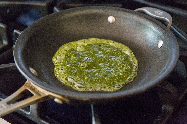 Add pesto sauce to a skillet and allow it to sizzle
