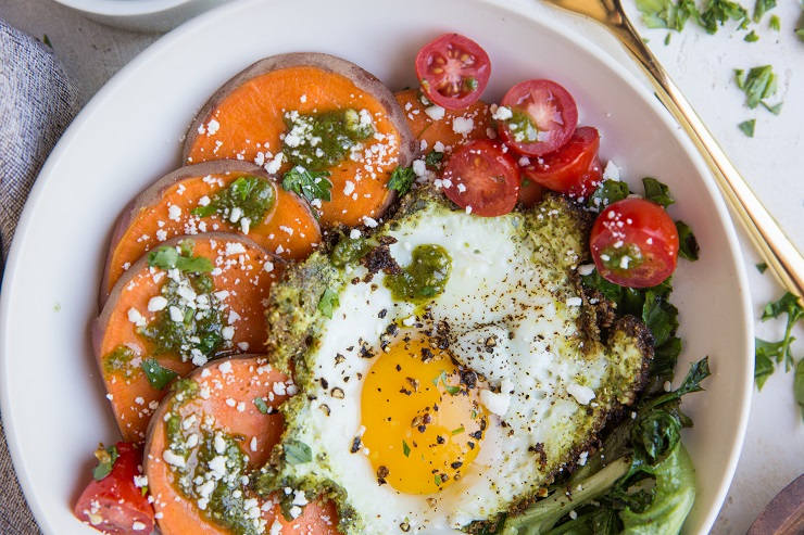 Pesto Eggs with Sweet Potatoes, Greens, and cherry tomatoes and feta cheese. A delicious breakfast bowl!