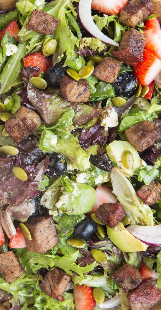 Amazingly flavorful Steak Salad with sweet tangy berries, creamy avocado and feta, Green Goddess Dressing, red onion, green onion, and pumpkin seeds. A unique and delicious healthy salad recipe!