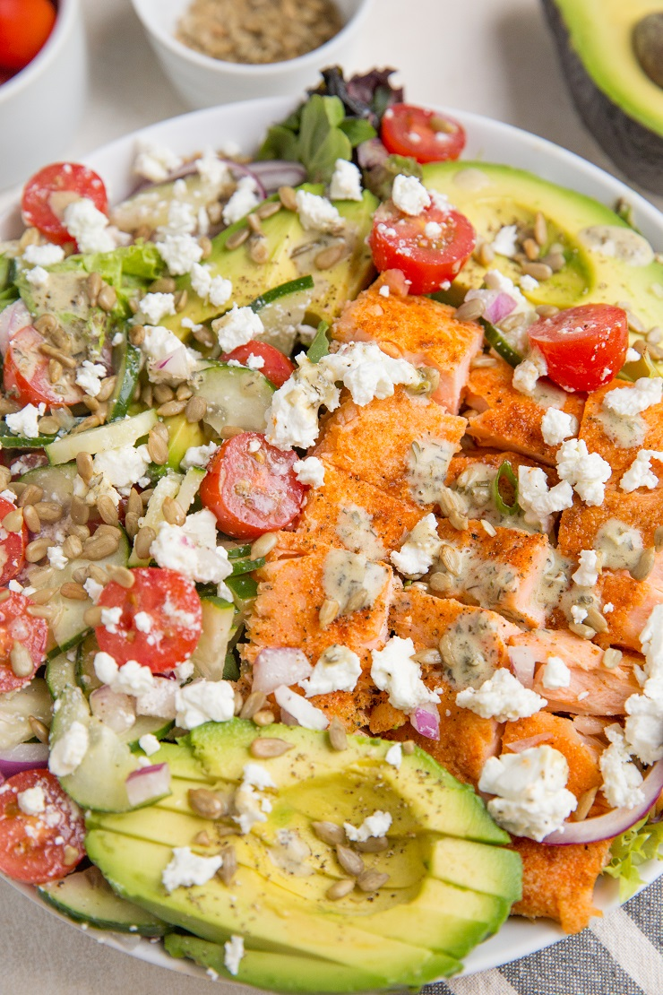 Greek Salmon Salad with Avocado, feta, cucumbers, tomatoes, red onion, and an herby dressing.