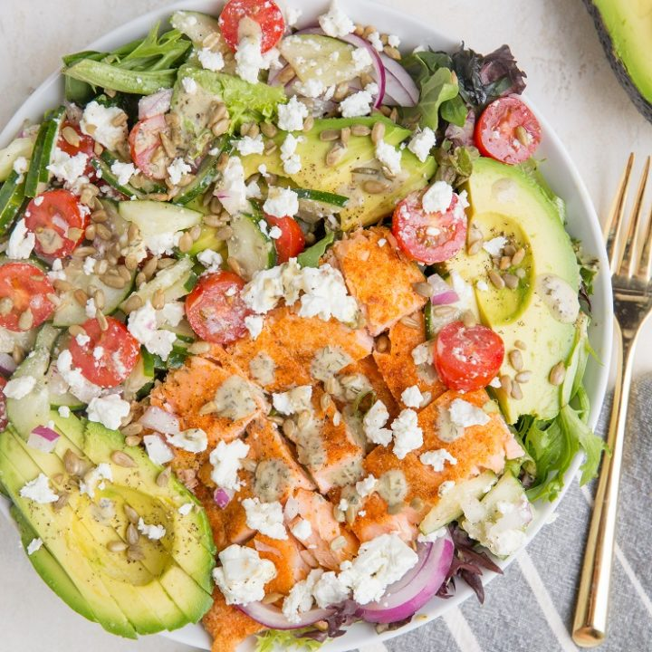 Greek Salmon Salad with spring greens, avocado, feta, sunflower seeds, cucumber, tomatoes, and an herby delicious dressing. Low-carb, delicious summer salad recipe.