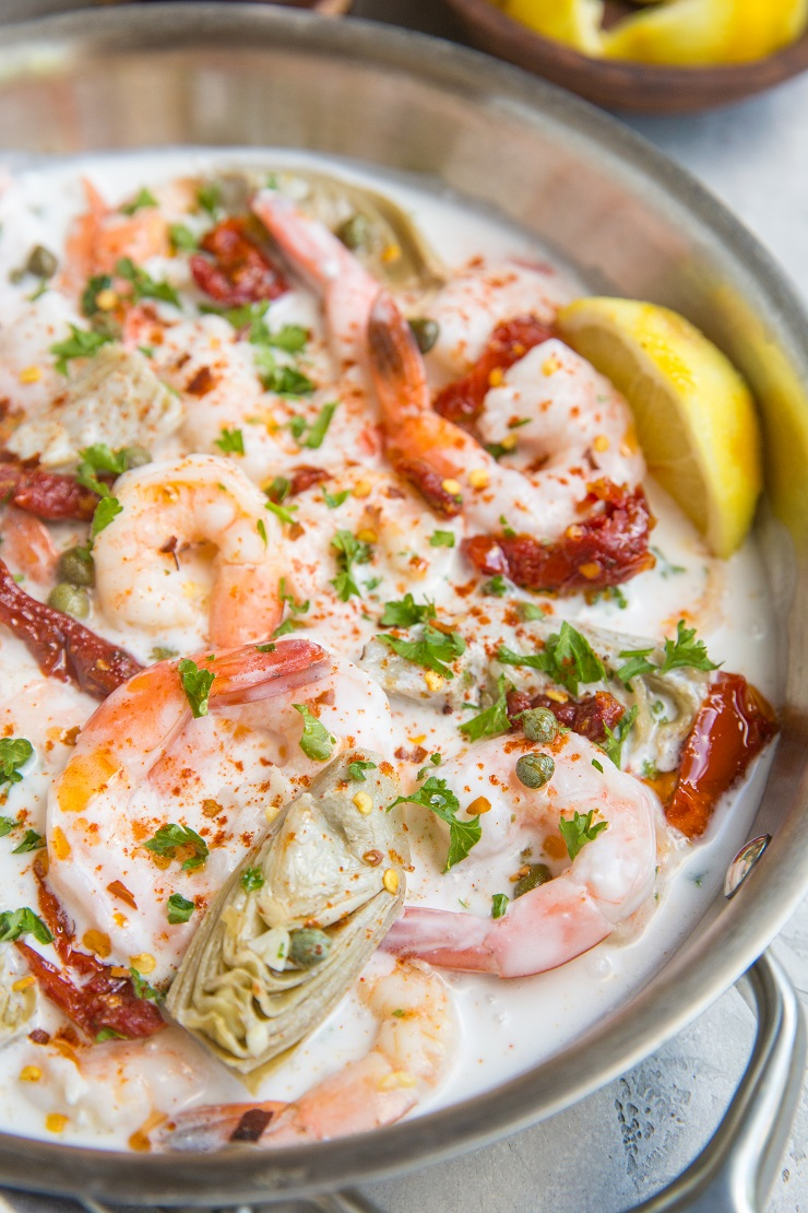Creamy Tuscan Shrimp Recipe with sun-dried tomatoes, artichoke hearts, and more! Dairy-free, paleo, whole30, keto and delicious!