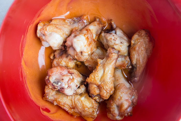 Put the cooked chicken in the bowl with the buffalo sauce.