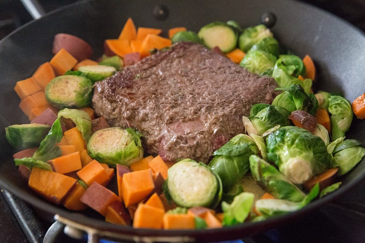 Add all of the ingredients for the recipe to a skillet, placing the ground beef in the center to brown
