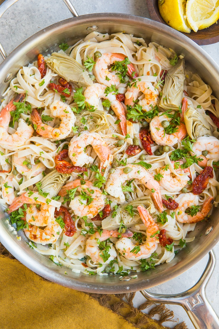 Easy Mediterranean Shrimp Pasta with capers, sun-dried tomatoes, artichoke hearts, and lemon garlic cream sauce. Gluten-free, dairy-free, light and healthy!