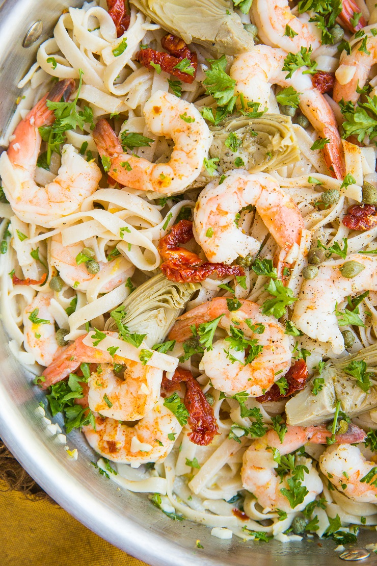 Mediterranean Shrimp Pasta with sun-dried tomatoes, artichoke hearts, capers, and lemon garlic cream sauce made gluten-free and dairy-free! A light and healthy pasta recipe!