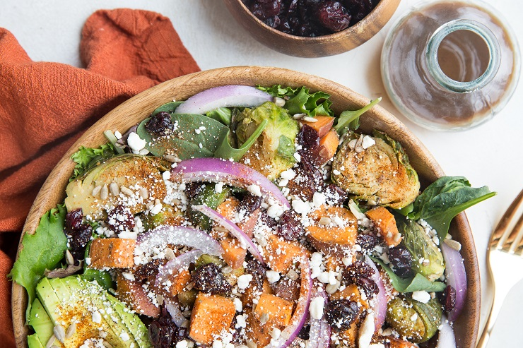 Nutritious superfood Roasted Sweet Potato and Brussel Sprouts Salad with cinnamon balsamic vinaigrette, avocado, dried cranberries, avocado, and more