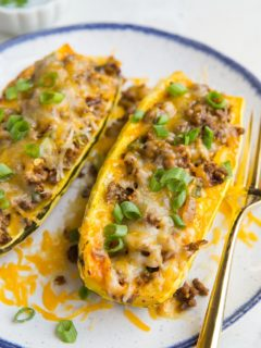 Taco Stuffed Delicata Squash with spiced ground beef, onion, and cheese. This simple, clean meal is nourishing, easy to prepare, and perfect for fall or winter!